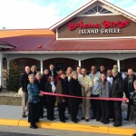 Prince William Chamber Members and Potomac Mills Mall staff, join Sufian Essawi (pictured with scissors) general manager of the Bahama Breeze Potomac Mills for their ribbon cutting.