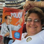 "Local Rotary club member Debbie Edenhart holds an ""End Polio Now"" cartoon book during an outing at Nationals Park."