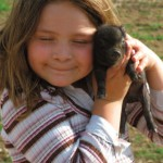 "Sierra Smith, 8, shows her affection for one of the piglets on her family's farm, a fully-operational ""Virginia Century Farm"" that pasture-raises animals without hormones or animal byproducts."