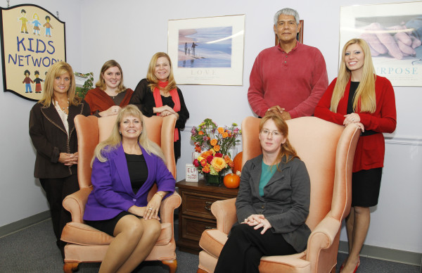CASA CIS staff members (left to right) Toni Lightfoot, Laurel Schaepman, Sheryl Rogers, Ben Gimeno and Brook Norgart.  Seated, Sharlyn Hasson-Brown and Tara Reber. Photo courtesy Robert Arnold, Realistic Art Photography