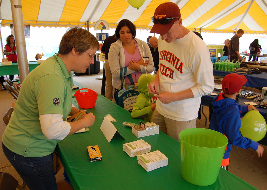 "Public Works Employee Deb Oliver explains the ""I Recycle"" Pledge to guest at Prince William Recycles Day event at the landfill in October."
