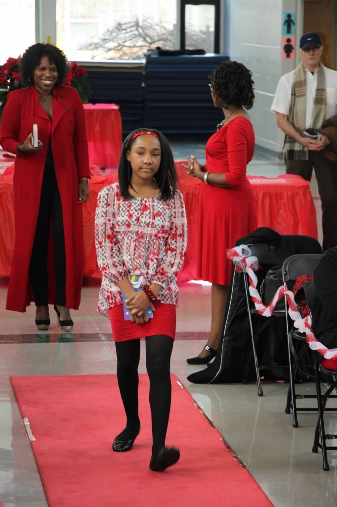 Young author Candace Todd strides down the red carpet as seasoned author Victoria Christopher Murray looks on with admiration.