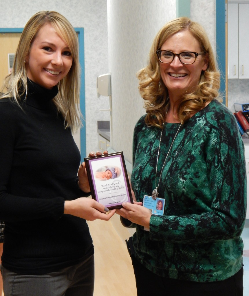 Ann Heberer (left) of Sentara Northern Virginia Medical Center accepts the March of Dimes Day of Gratitude plaque on behalf of the NICU staff.