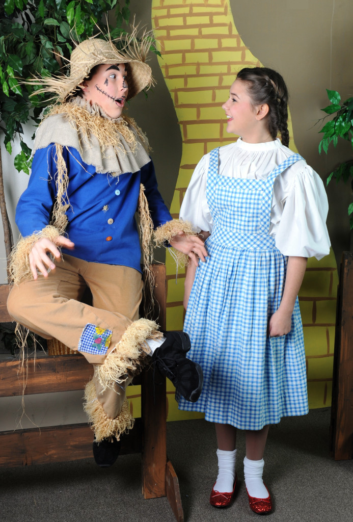 Dorothy (Grace Klebine) meets the Scarecrow (Danny Waldman) sitting on a fence in Pied Piper Theatre's The Wizard of Oz.