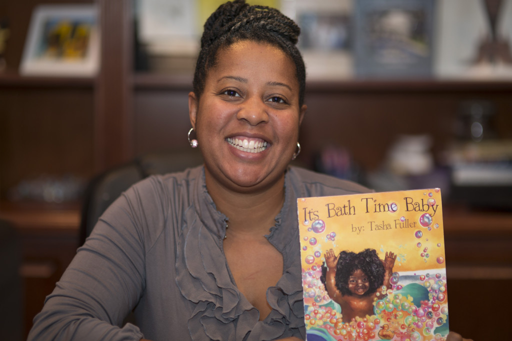 """Woodbridge resident and author Tasha Fuller holds a copy of """"It's Bath Time Baby,"""" a children's book based on a rhyme she created and sang to her daughter."""
