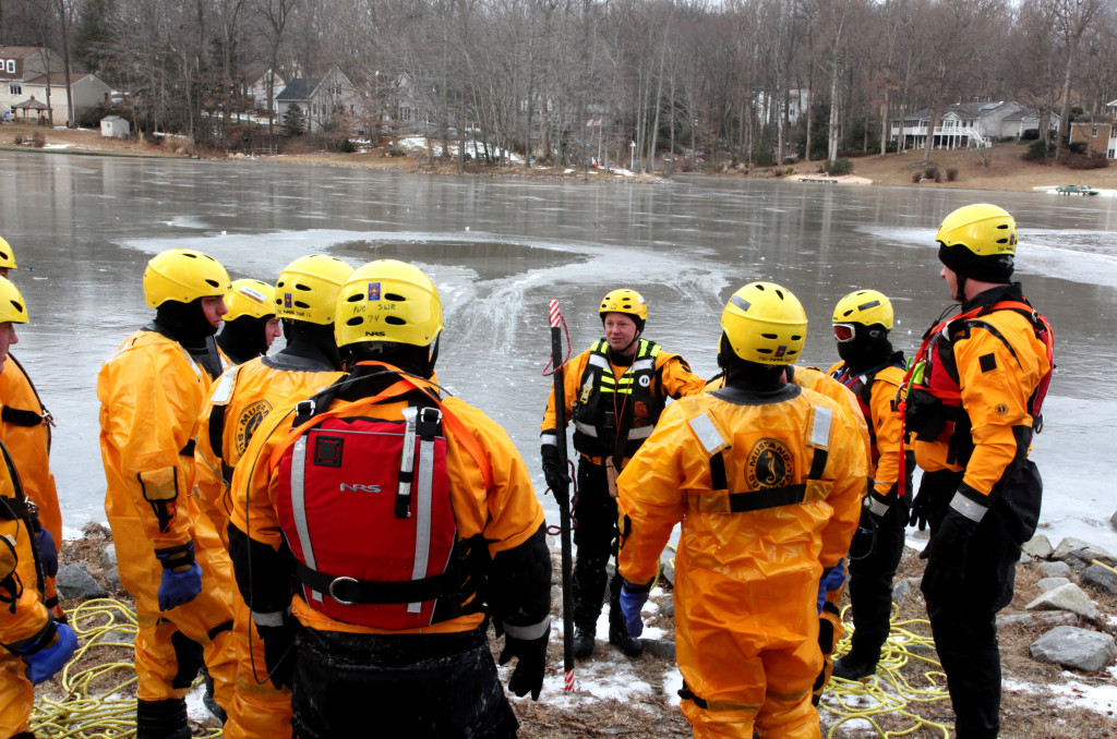 Lt. Phil Miller, center, of the Prince William Fire and Rescue Swift Water and Flood Rescue Team, briefs other team members about what they will be doing as they practice their ice rescue techniques Tuesday at Lake Montclair. It's been several years since it's been cold enough for the team members to practice their techniques and procedures under real-world, icy conditions.