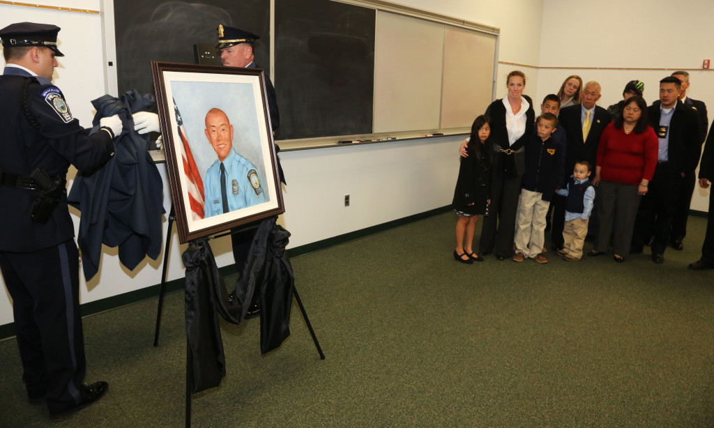 Officer Chris Yung's family looks on as his portrait is unveiled during a ceremony at the Prince William County Public Safety Training Center. Yung died in a traffic accident last year as he rushed to help others who were involved in a separate accident at Va. 28 and Piper Lane.