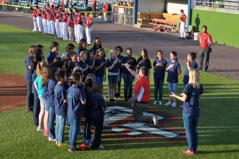 The Potomac Nationals invite the community to share the spotlight at Pfitzner Stadium.  Here, the singing scribes of Penn Elementary School in Dale City, led by music teacher Talia Roder, perform the National Anthem before a recent game.