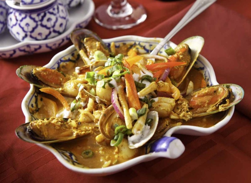 The entree House Seafood includes stir-fried mussels, squid, shrimp and scallops mixed with bell peppers, onions, celery, scallions and egg in a house coconut yellow curry sauce.