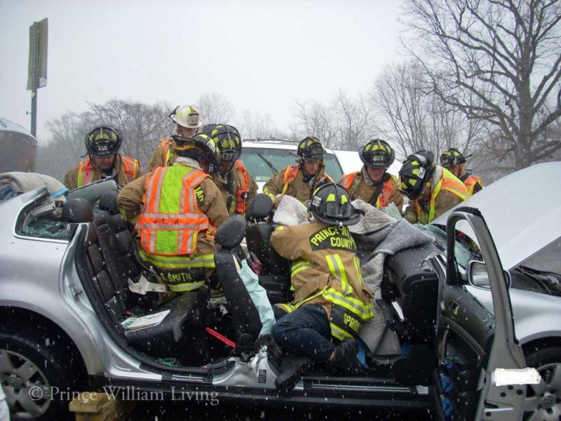 Prince William County Department of Fire & Rescue personnel work together to extract a driver from the wreckage of his vehicle.