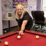 Trillium Drop-In Center Executive Director Cynthia Dudley shoots a game of pool in Trillium's recreation room.