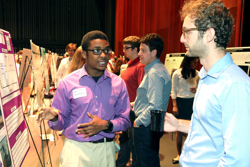 Kelechi Nwanevu, left, a Forest Park High School rising senior, talks with Ruben Magni, a research affiliate at the Center for Applied Proteomics at George Mason University, during a gathering at the Hylton Performing Arts Center where the young researchers exhibited the work they did during George Mason University's Aspiring Scientists Summer Internship Program.