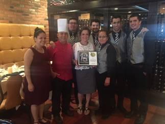 Alice Pires, owner of Carmello's (center with plaque) with Carmello's staff of Historic Manassas, Va.