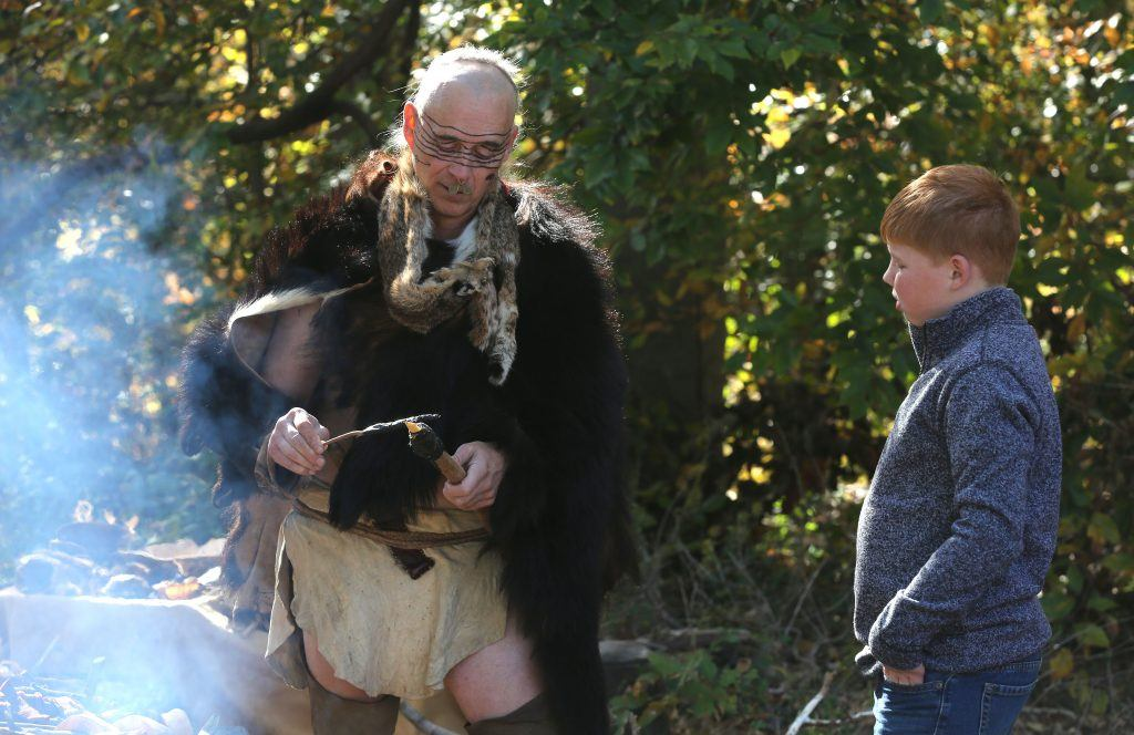 """Doug Wood a Dogue Indian reenactor, left, teaches Christophe Fries, 7, how the people of the Dogue tribe made spears of wood and bone at the recent """"Early Days of Prince William County"""" event at Rippon Lodge. The Dogue lived in the area when the first settlers came to the county"""