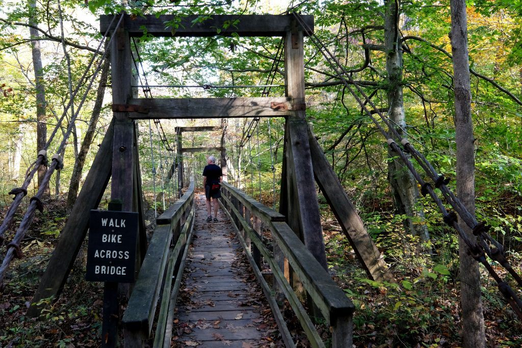 A hiker crosses a bridge along a trail in Prince William Forest Park.